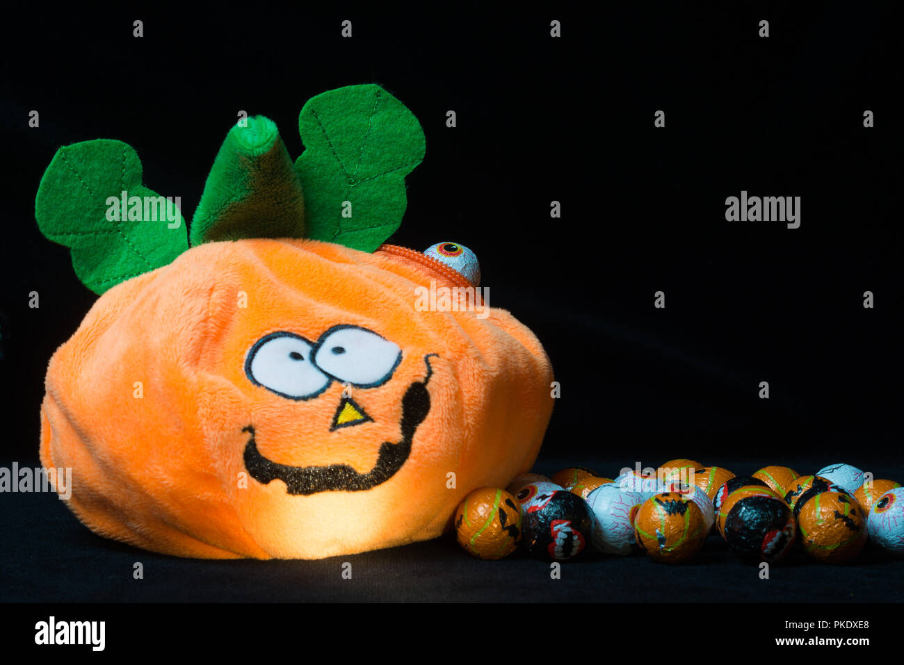 Divertente il giocattolo di peluche a forma di zucca di Halloween con i  lotti delle sfere di cioccolato intorno ad esso 40e91163a650