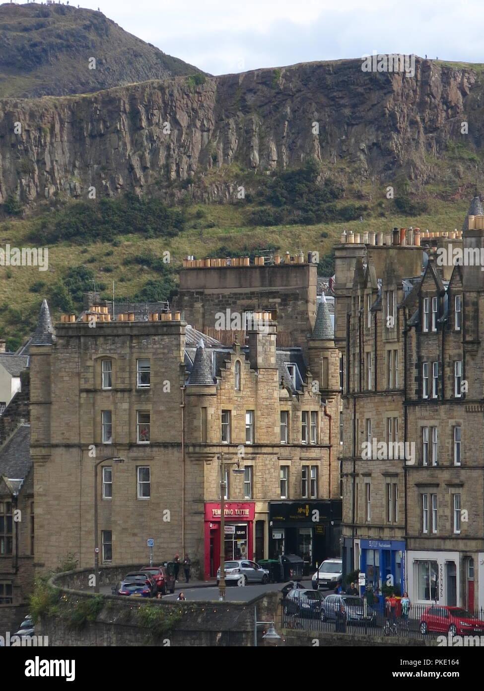 """Una strada di Edimburgo vista scena guardando giù Jeffrey Street verso Salisbury Crags; grand edifici in pietra e il rosso fiammante """"tentati Tattie' Immagini Stock"""
