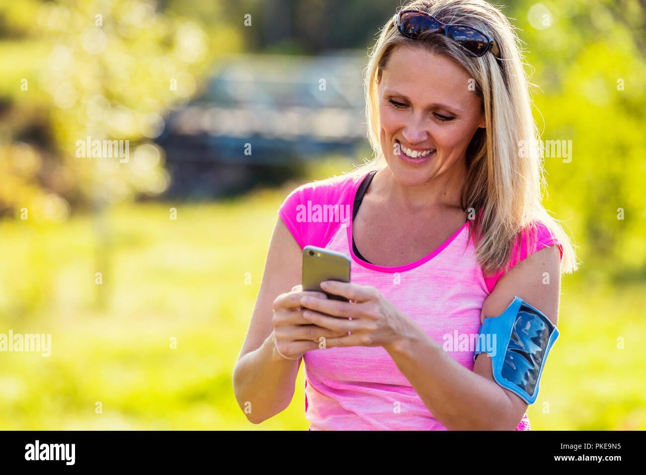 Una donna matura indossando active wear e una fascia da braccio per mantenere il suo smart phone testi prima di uscire per una corsa in un parco della città durante la stagione autunnale Immagini Stock