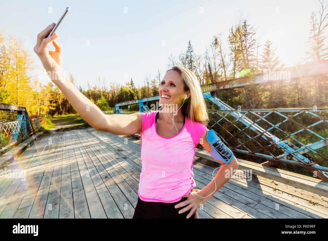 Una donna che indossa active wear e una fascia da braccio per il suo telefono cellulare si erge su un ponte in un parco in autunno prendendo un autoritratto con il suo telefono cellulare Immagini Stock
