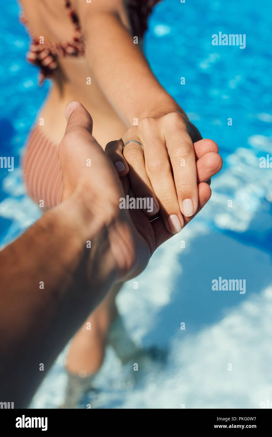 Ritagliato shot di man mano tesa della moglie in piscina, follow me concetto Immagini Stock