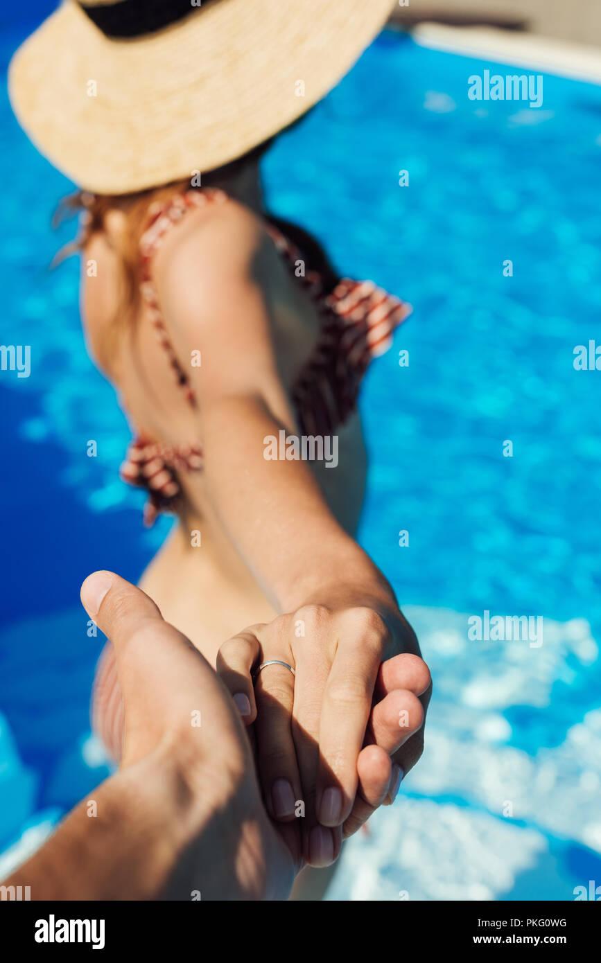 Ritagliato shot di man mano tesa della giovane moglie in piscina, follow me concetto Immagini Stock
