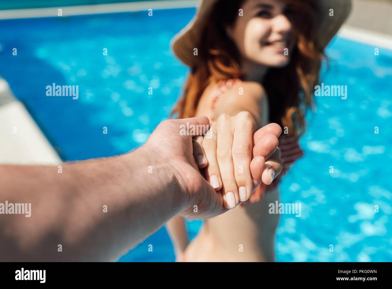 Ritagliato colpo di azienda man mano di sua moglie felice in piscina, follow me concetto Immagini Stock