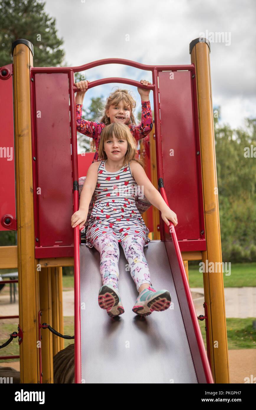 Due ragazze in una sequenza di divertirsi e giocare in un parco giochi. Immagini Stock