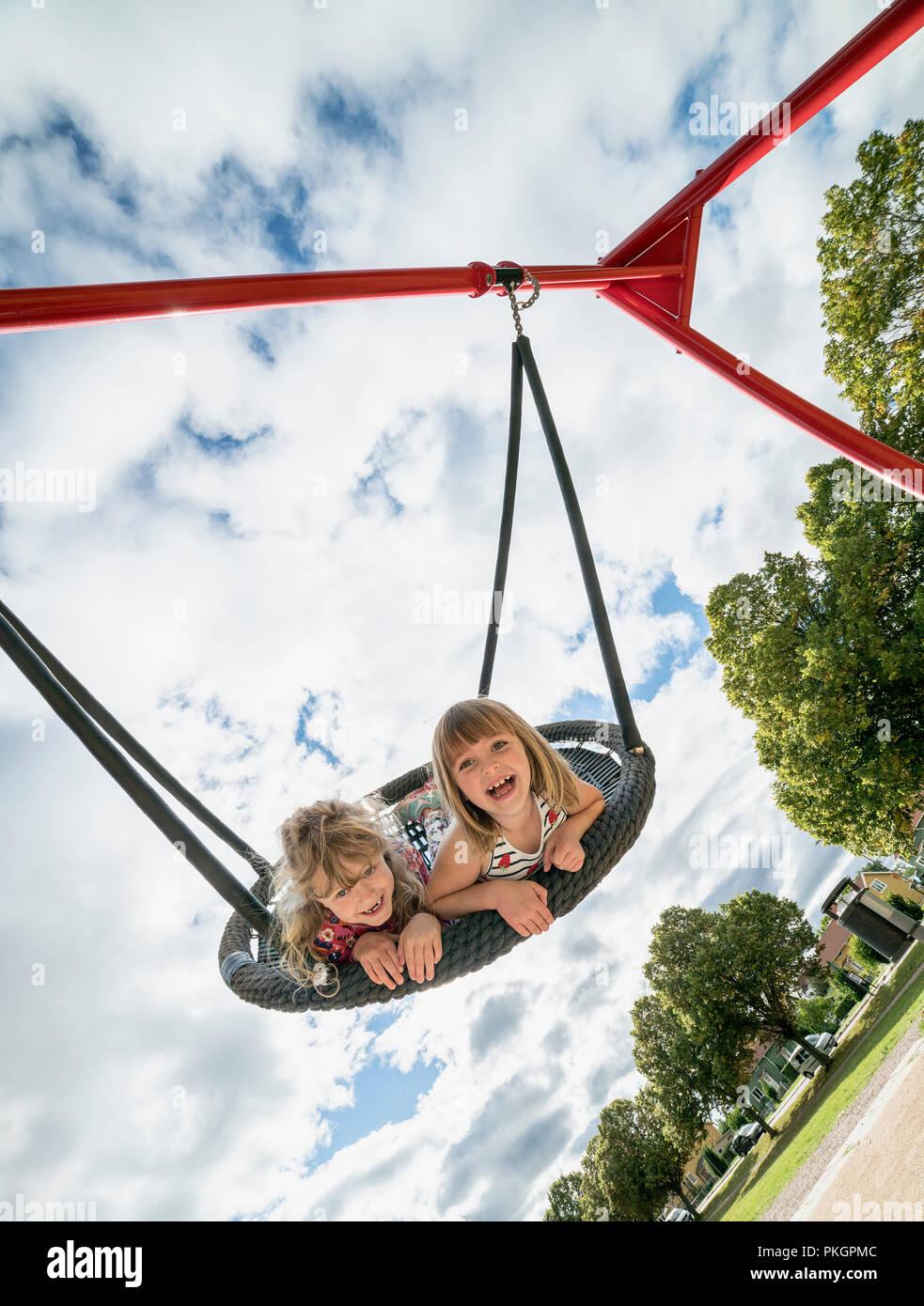 Due giovani ragazze in un altalena divertendosi e giocando in un parco giochi. Immagini Stock