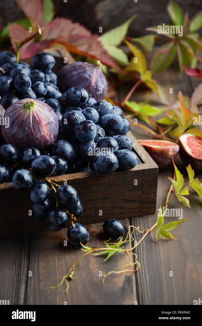 Fresca uva nera e figure in legno scuro vassoio sul tavolo di legno messa a fuoco selettiva Immagini Stock