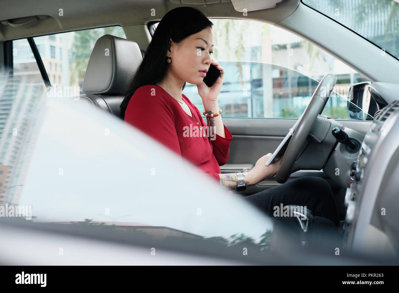 Efficiente femminile cinese manager che lavora in auto. Successo imprenditrice asiatici sorridente e parlando al cellulare. Immagini Stock