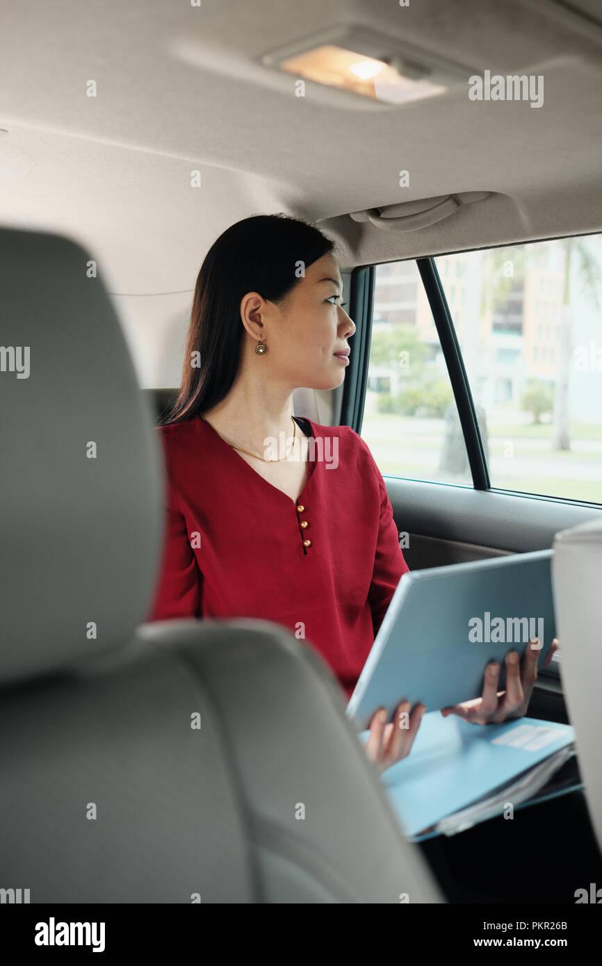 Femmina cinese manager che lavora in auto mentre il pendolarismo per lavoro. Successo imprenditrice asiatici utilizzando il computer portatile e l'equitazione taxi. Immagini Stock