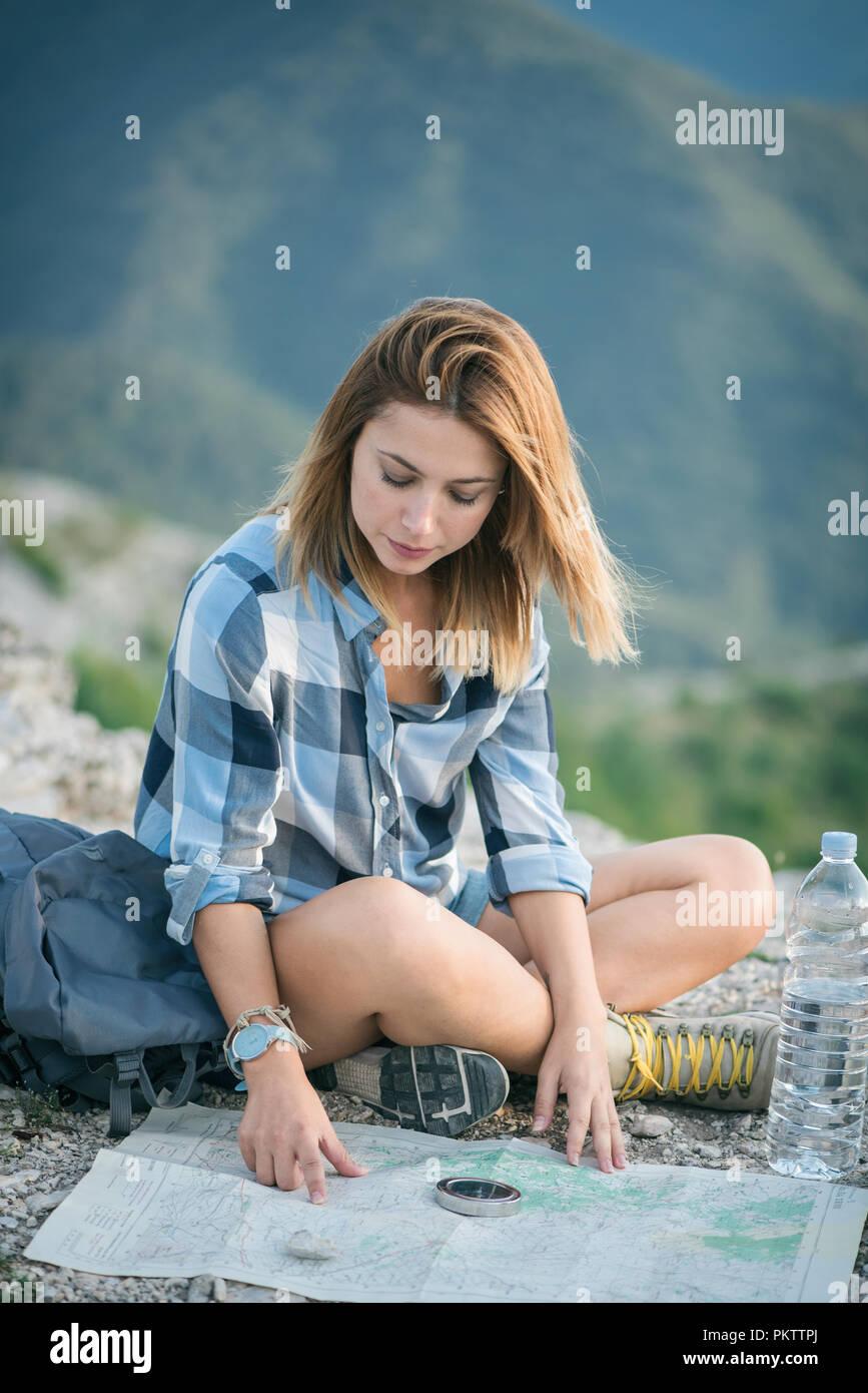 Giovane donna mappa di lettura in montagna Immagini Stock