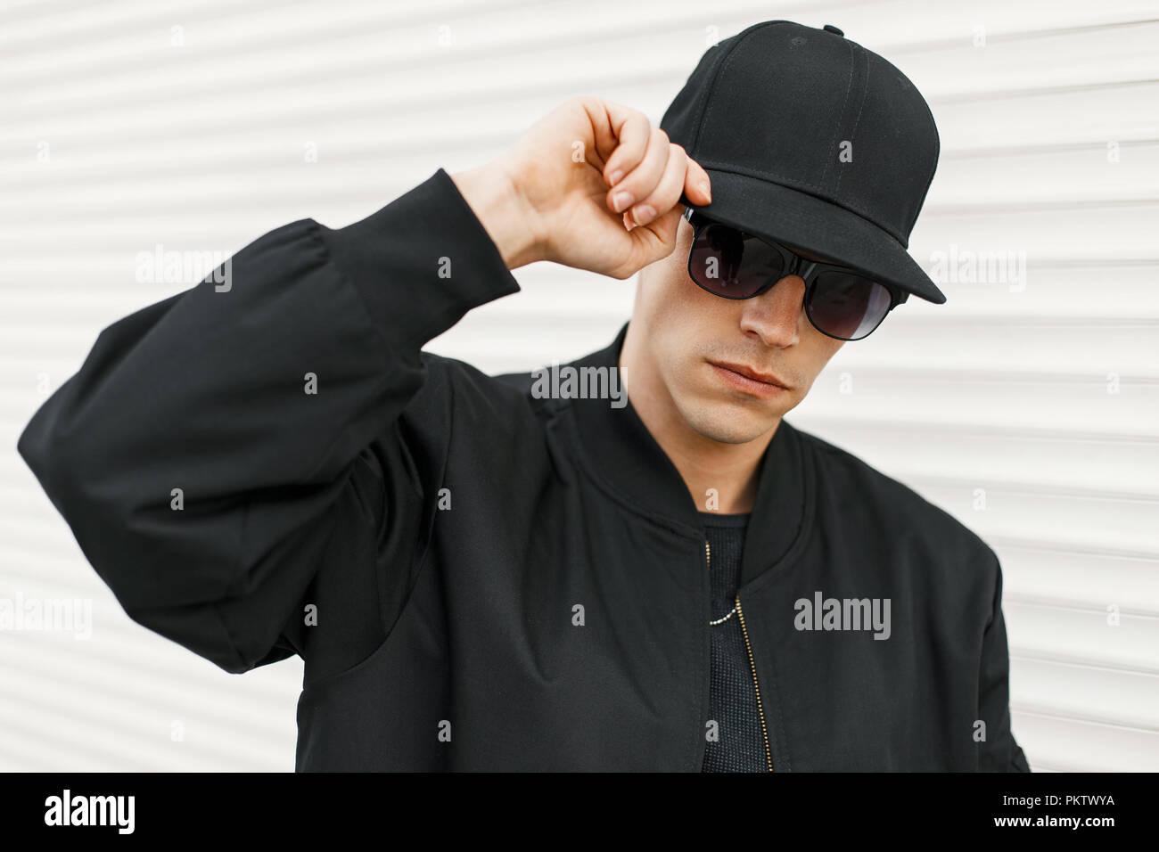 Uomo bello con nero occhiali alla moda e un nero cappello da