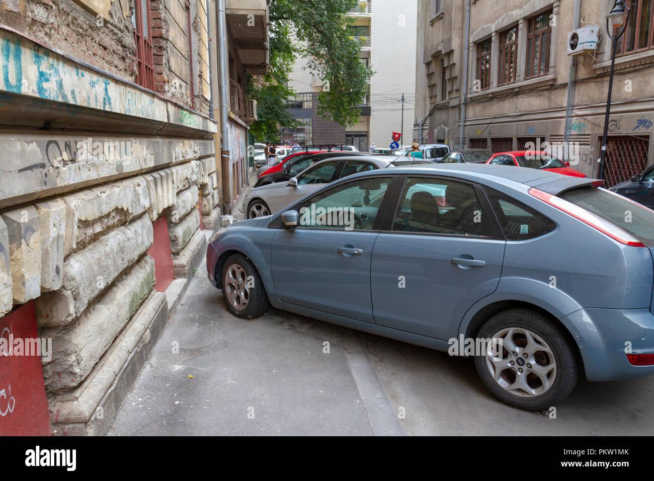 Tipico pavimento parcheggio auto nel centro di Bucarest, Romania. Parcheggio sui marciapiedi, in corsie di guida & bloccando gli altri è normale in Bucarest. Immagini Stock