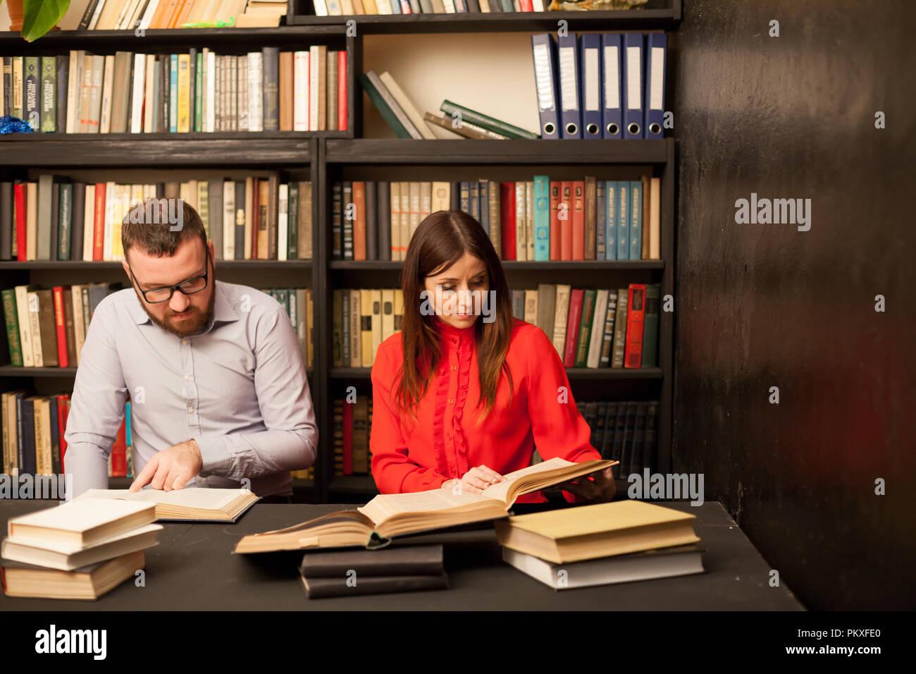 Un uomo e una donna per leggere i libri in biblioteca sono la preparazione per l'esame 1 Immagini Stock