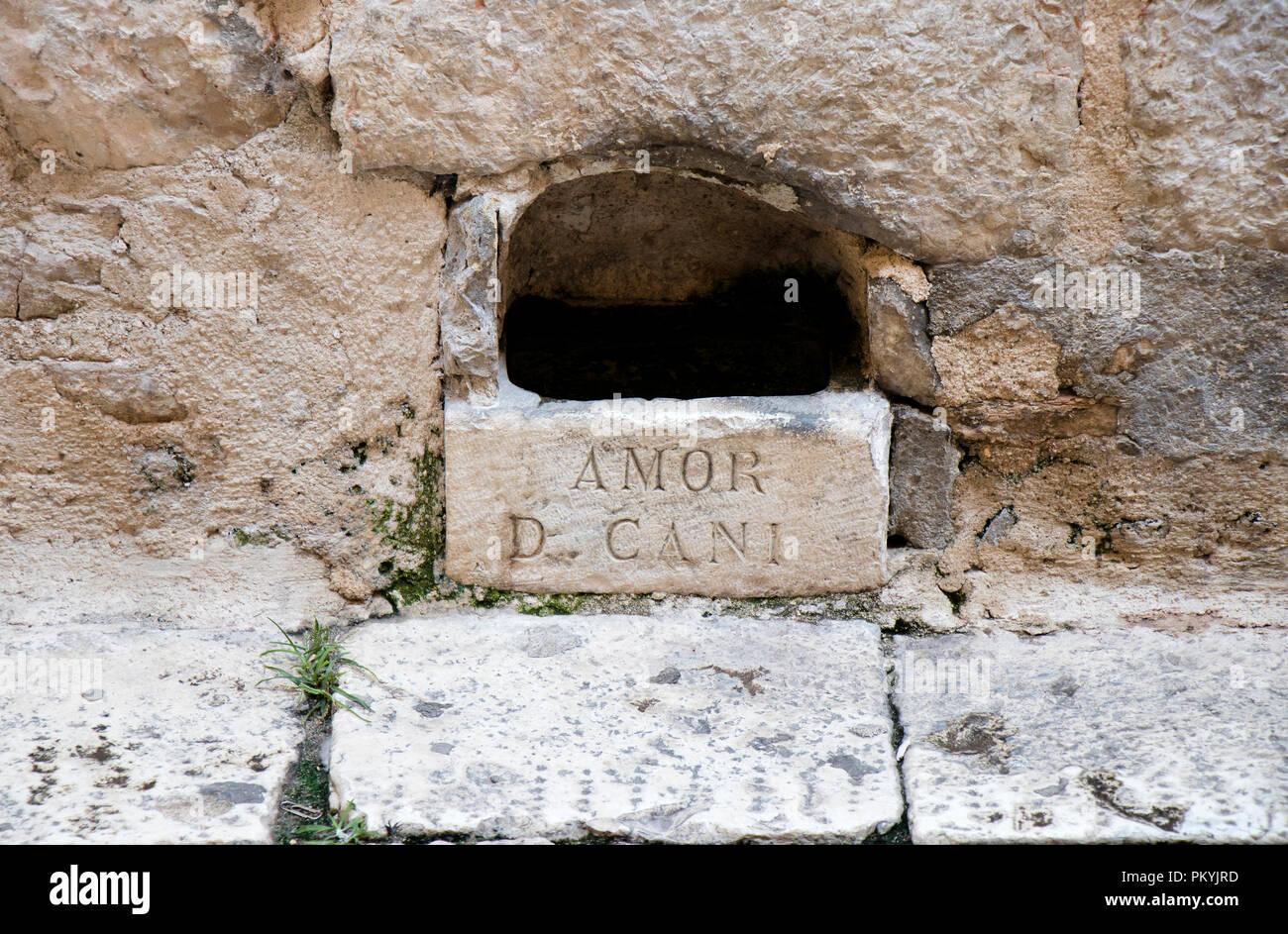 Foro di irrigazione , pietra ciotola fatta nella parete di facciata della casa nella città vecchia di Sebenico Main Street, con segno latino AMOR D CANI , era uomo-realizzato per fornire dri Immagini Stock