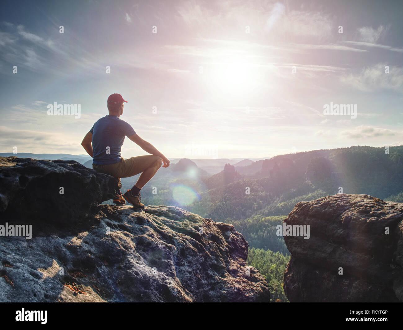 Escursionista guardando al sole all'orizzonte. Bel momento il miracolo della natura. Nebbia colorata in valle. L'uomo escursione. Immagini Stock