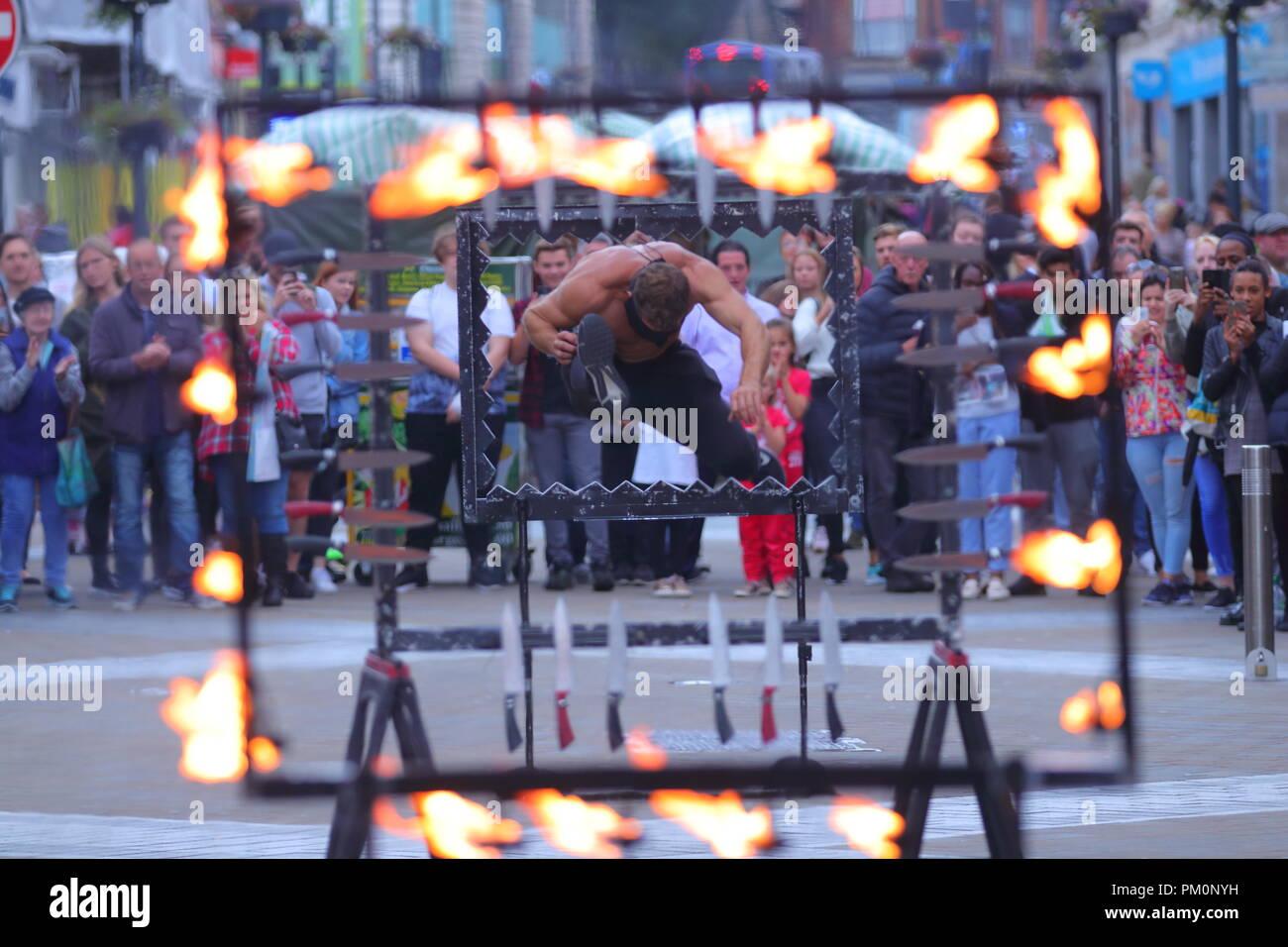 Un diavolo osano getta la sua auto attraverso i coltelli affilati & fire mentre gli occhi bendati come parte del suo teatro di strada agiscono su BRIGGATE, Leeds, West Yorkshire. Immagini Stock