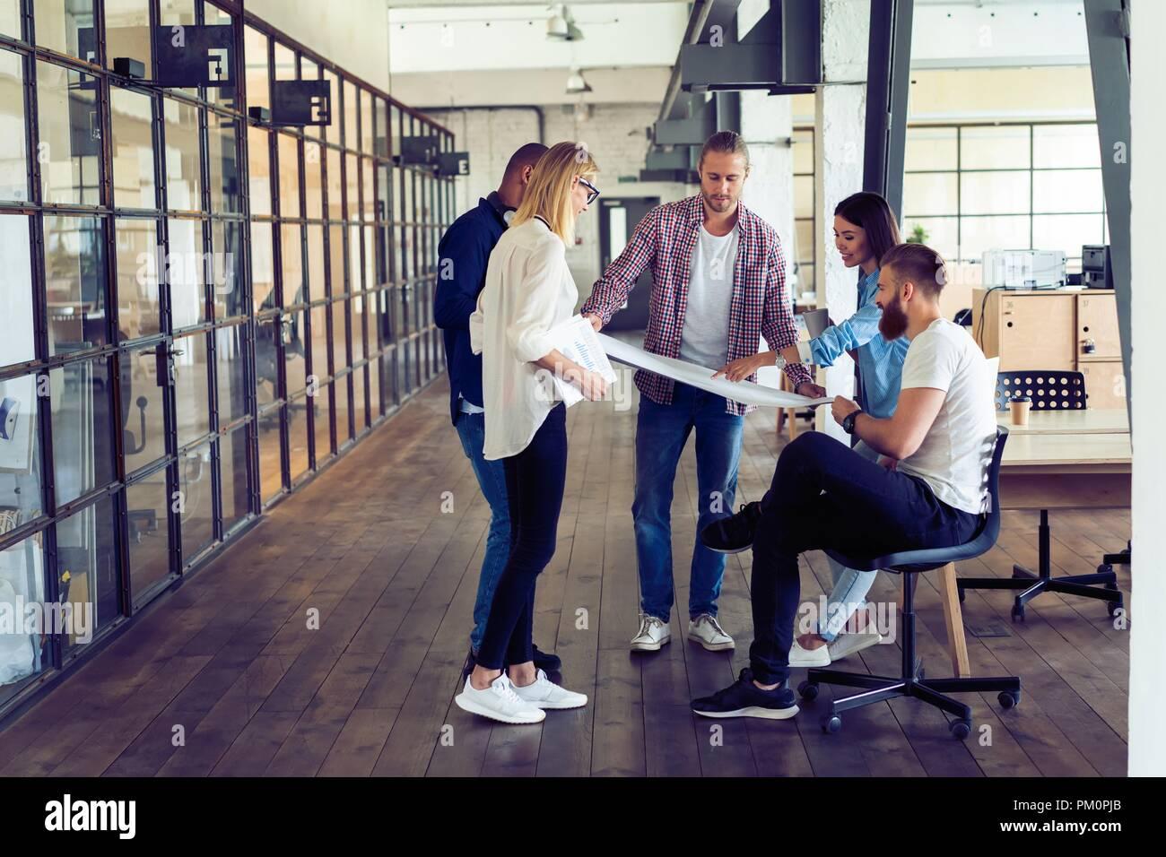 Un lavoro di squadra. Per tutta la lunghezza della giovane gente moderna in smart casual pianificazione della strategia di business mentre la giovane donna puntando al grande carta in ufficio corridoio. Immagini Stock