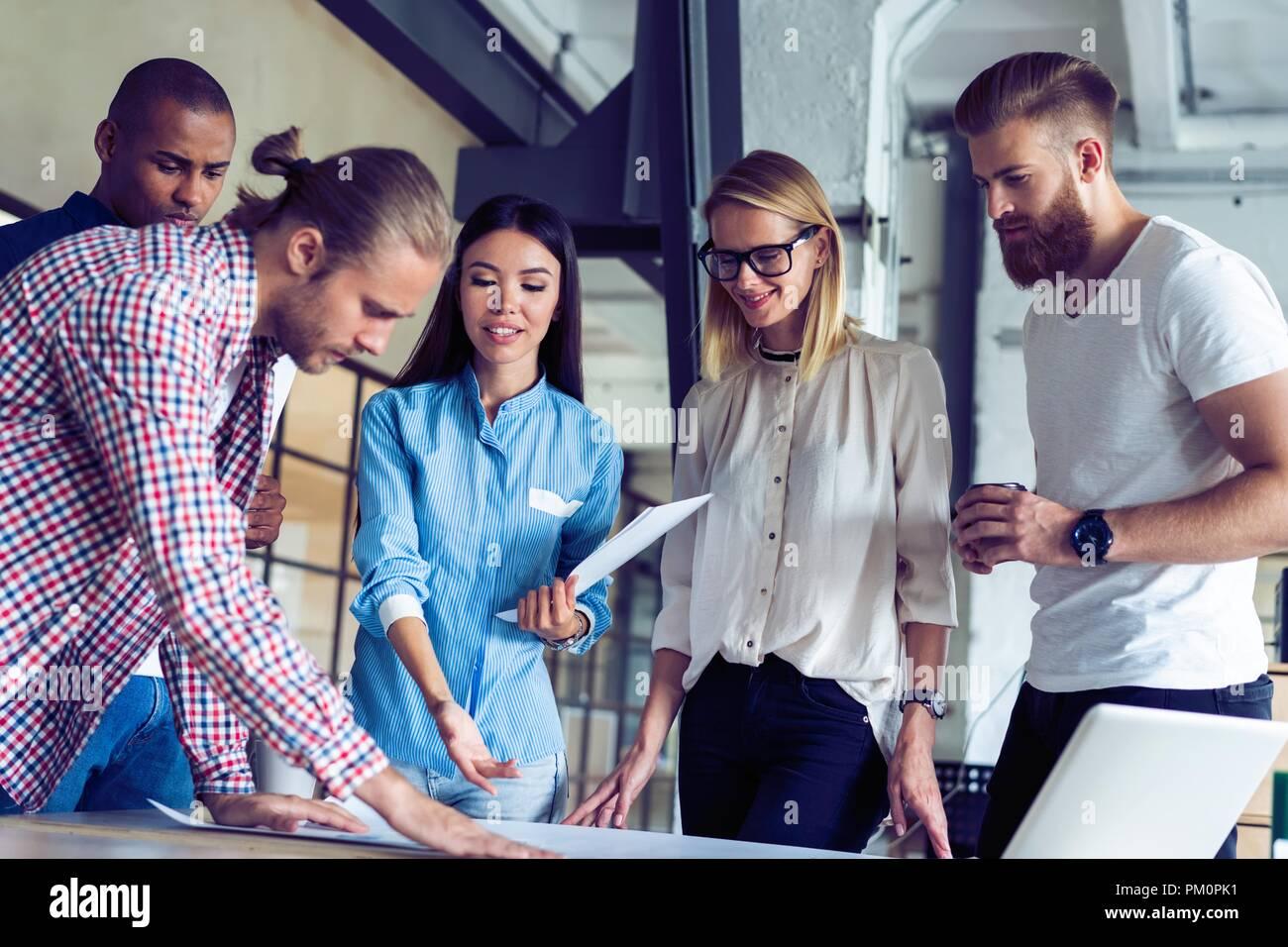 Successo di squadra. Un gruppo di giovani uomini di affari di lavoro e comunicare tra loro in ufficio creativo. Immagini Stock
