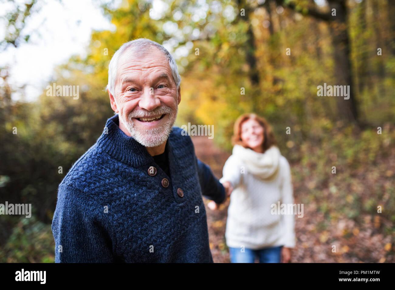 Un ritratto di una coppia senior passeggiate in una natura d'autunno. Immagini Stock