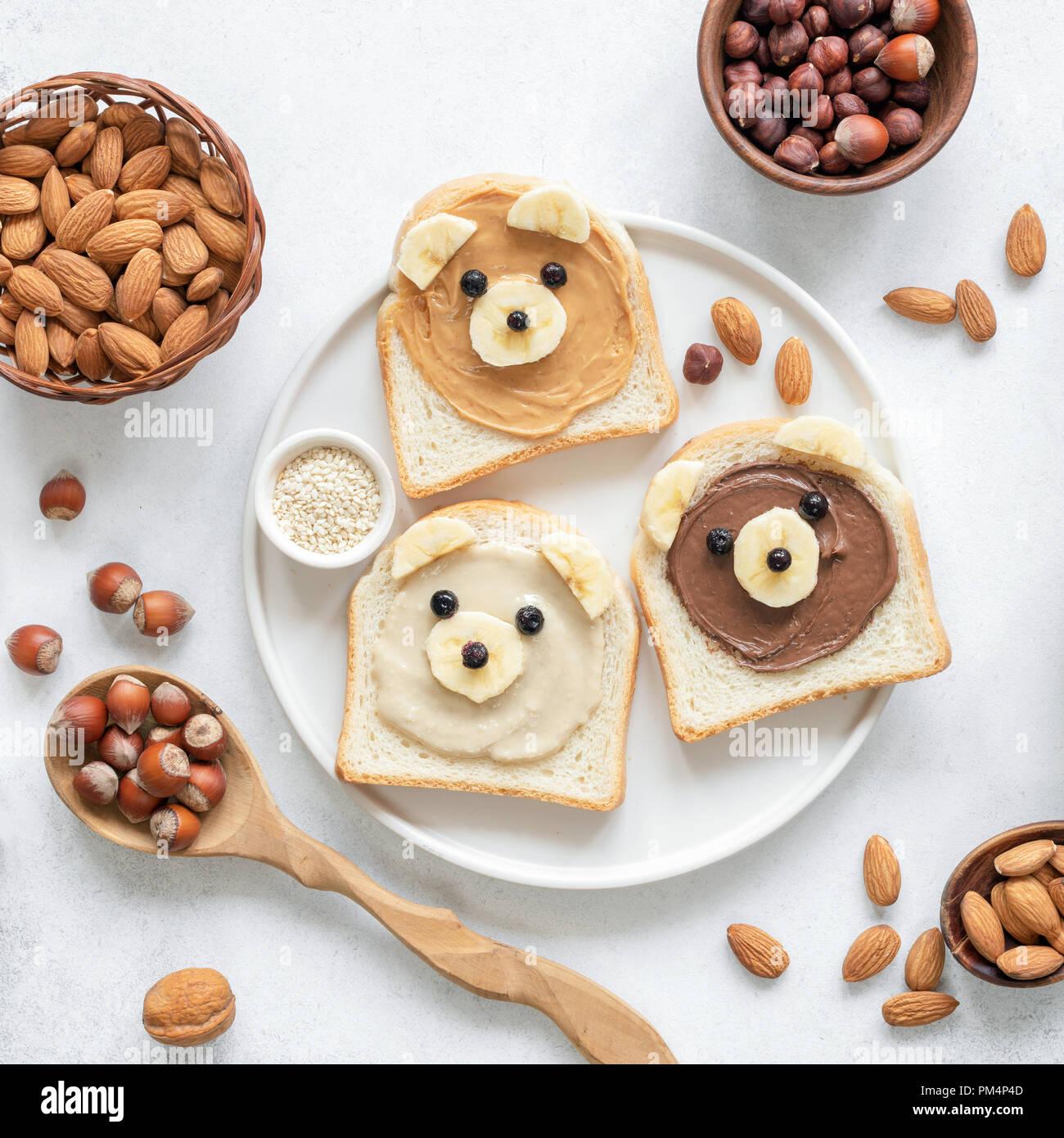 Il dado burro toast nella forma del simpatico orso divertenti per bambini serviti su una piastra bianca. Vista dall'alto. Cucina creativa arte, prima colazione per i bambini, scuola di concetto di pranzo Immagini Stock