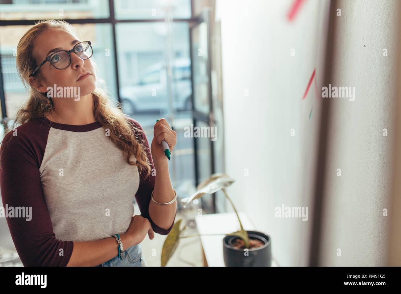 Giovane donna in piedi in ufficio e guardando la scheda di presentazione del pensiero. Femmina programmatore computer pensando su nuovo piano di progetto al tech start Immagini Stock