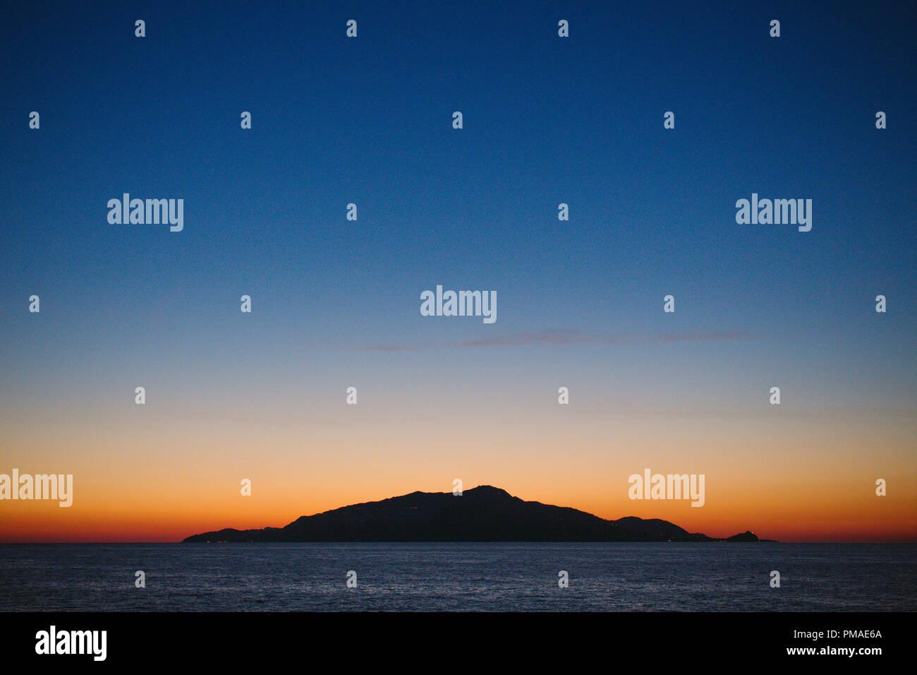 Una piccola isola deserta in mezzo all'oceano isolato all'orizzonte contro una luminosa arancione tramonto. Silhouette. Immagini Stock