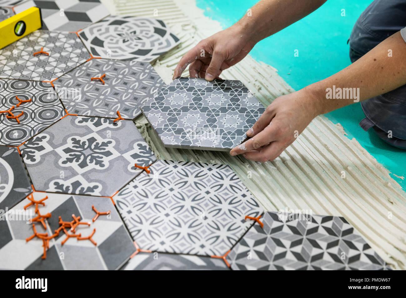Pavimenti uomo posa mattonelle esagonali sul pavimento foto