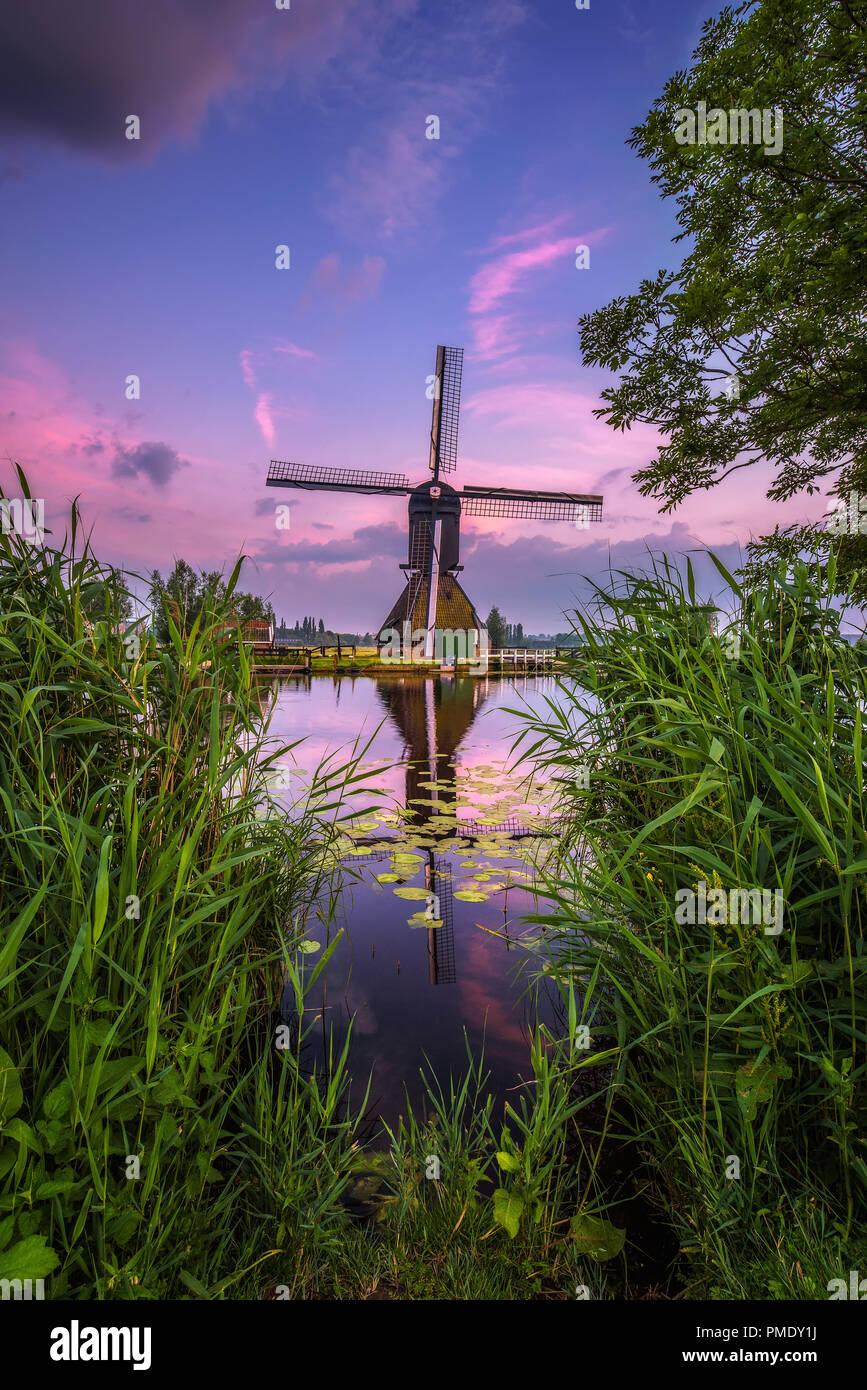 Il vecchio mulino a vento olandese e da un canale al tramonto in Kinderdijk, Paesi Bassi. Questo sistema di 19 mulini a vento è stata costruita intorno al 1740 ed è patrimonio UNESCO. Immagini Stock