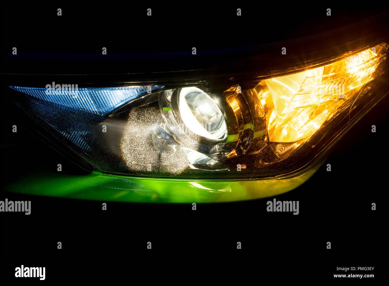 Faro anteriore su una moderna verde auto a notte. Anabbaglianti e luci indicatori di direzione lampeggiatore o lit. Foto Stock