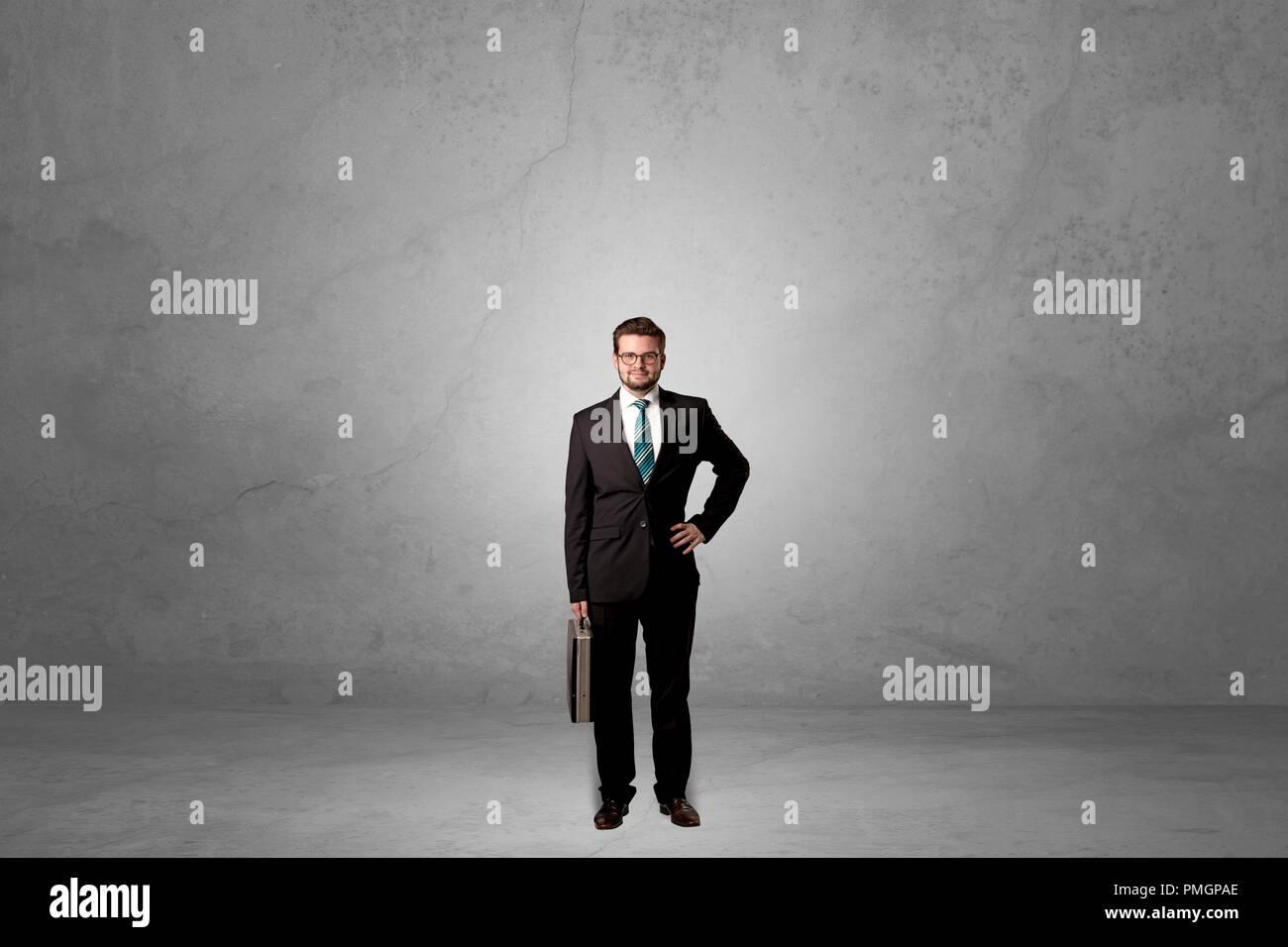 Solo imprenditore bello in piedi in una buia stanza vuota Immagini Stock