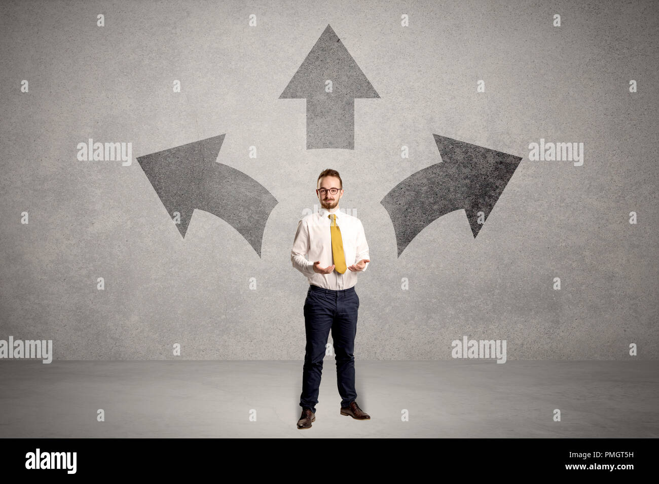 Affascinante imprenditore nel dubbio, scegliendo tra tre direzioni di fronte a un muro grigio Immagini Stock