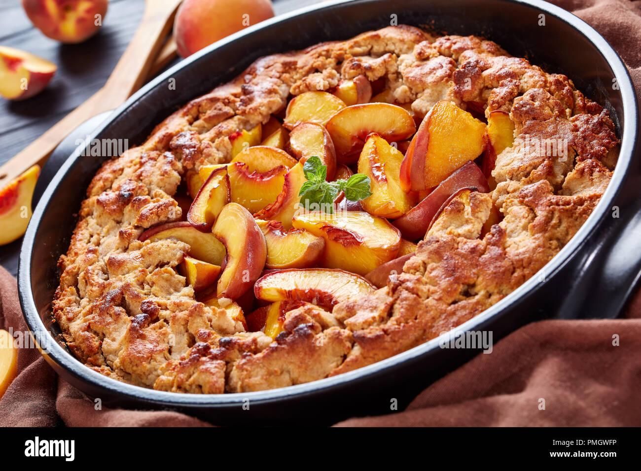 Peach Cobbler un profondo-piatto dessert di frutta, buono per la colazione cucinata in anticipo pasto, close up Immagini Stock