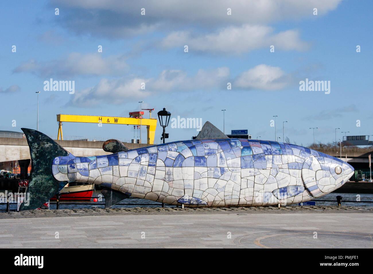 Il grande pesce o salmone della conoscenza, una scultura creato da John gentilezza a Belfast, Irlanda del Nord con uno di Harland e Wolff gru dietro Immagini Stock