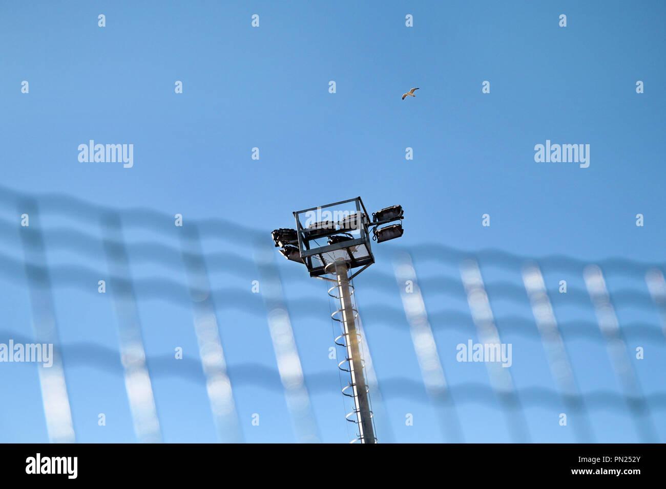 Lo stadio di torre dei proiettori con riflettori con cielo blu. palo