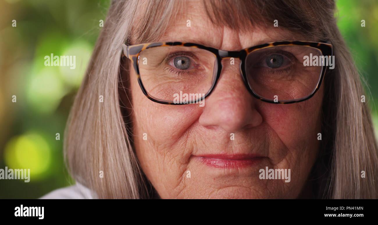 Stretto colpo di cupa donna matura indossando occhiali al di fuori in un lussureggiante ambiente Immagini Stock