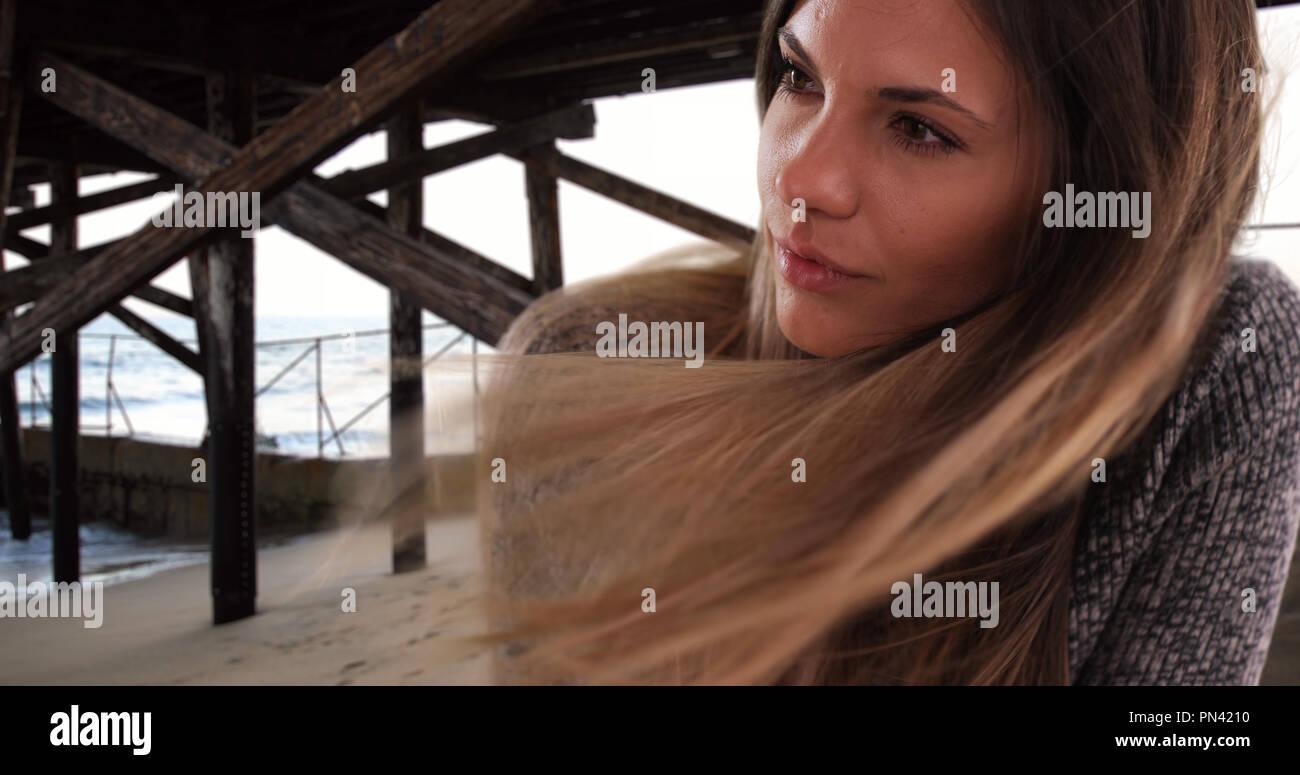 Bella donna con capelli lunghi marrone al vento dal molo presso la spiaggia  Immagini Stock 8552a635f8e0