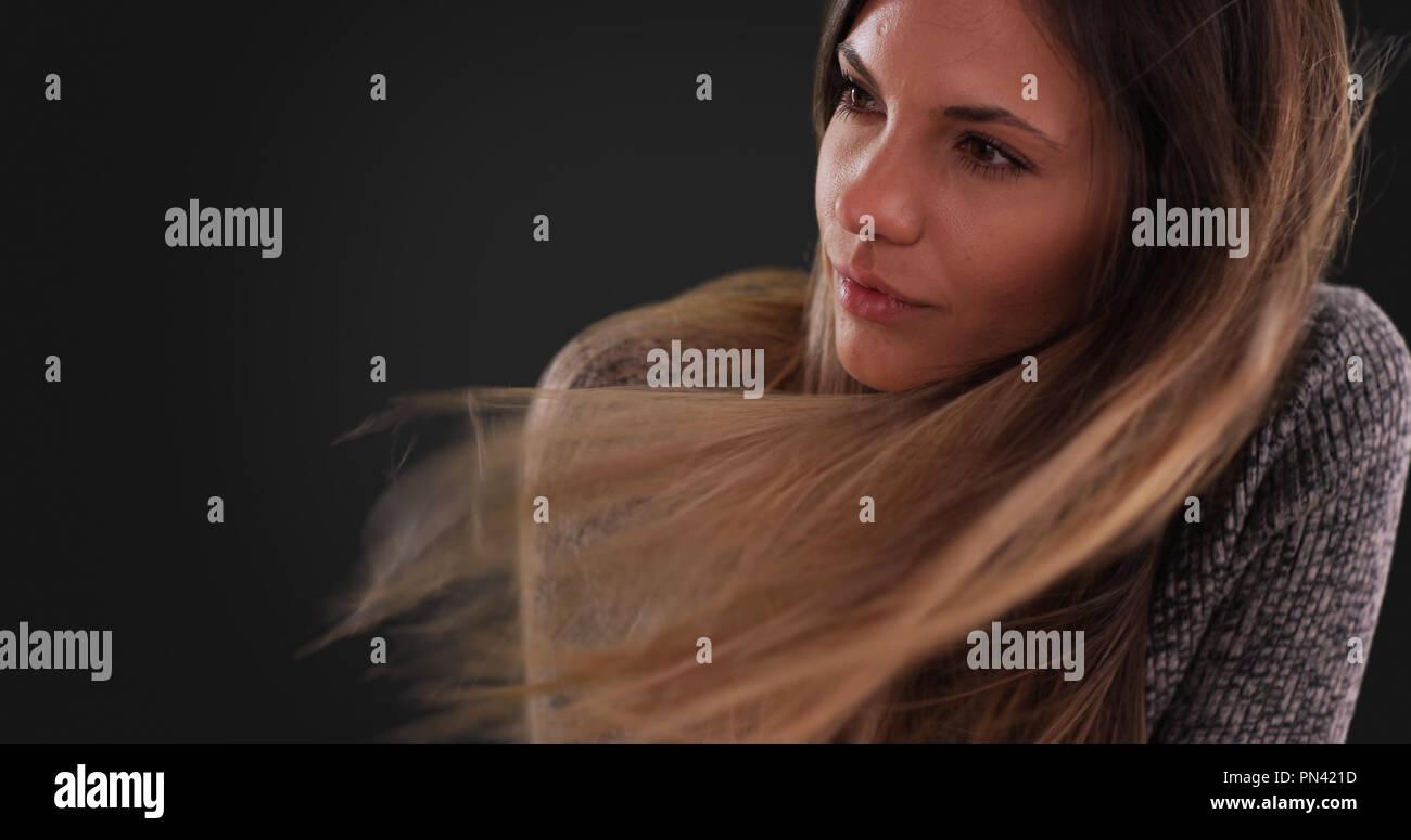 Bella donna con capelli lunghi marrone al vento su sfondo grigio ... 3efb9fbdc859