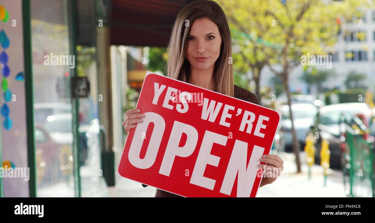 Proprietario di piccola impresa tenendo aperte segno guardando la fotocamera al di fuori del suo negozio Immagini Stock