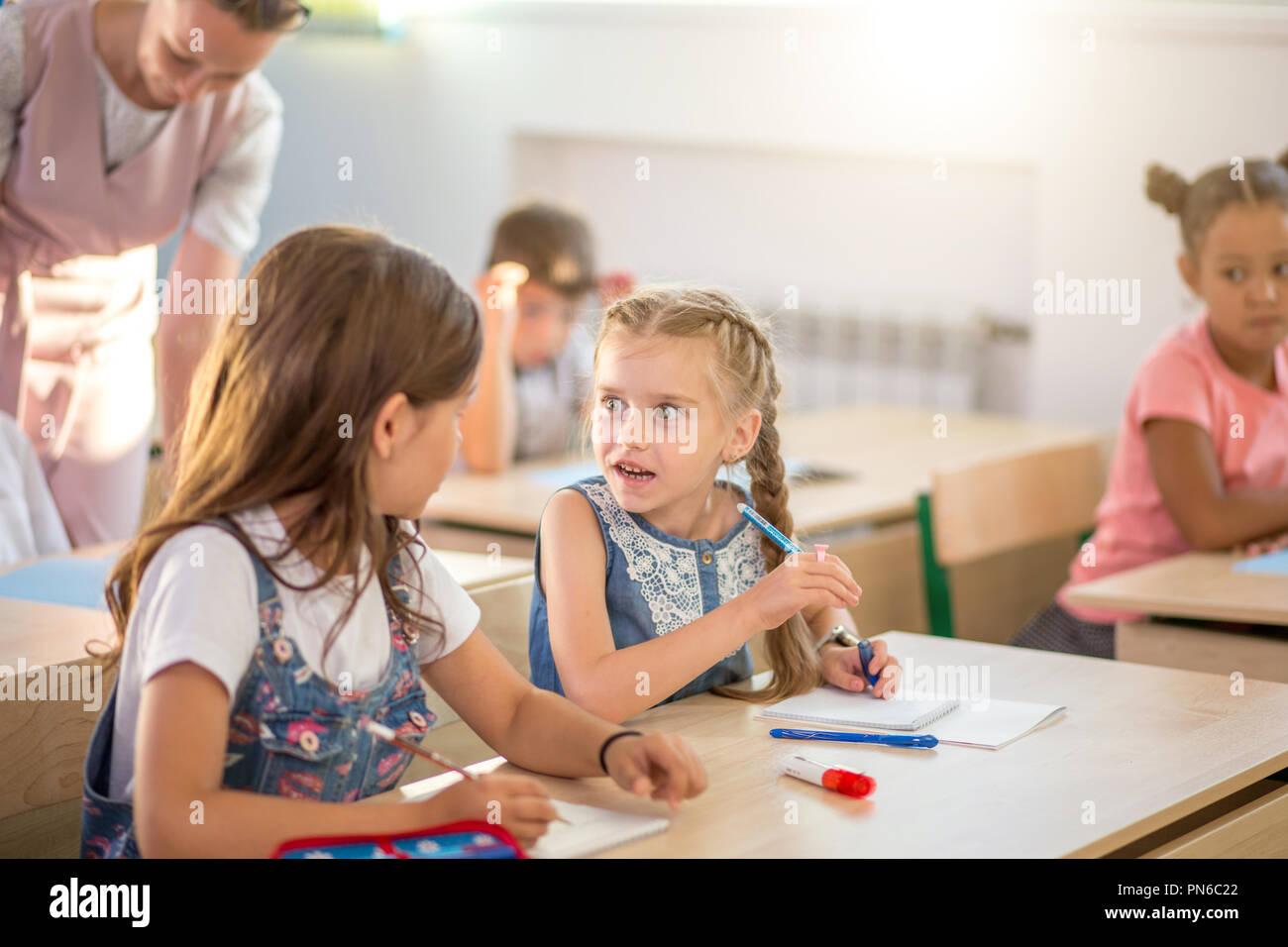 A scuola i bambini partecipano attivamente in classe. Istruzione, compiti concept Immagini Stock