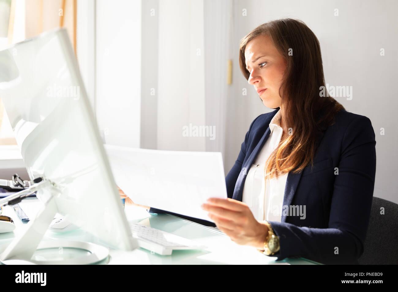 Concentrato giovane imprenditrice guardando i documenti di Office Immagini Stock