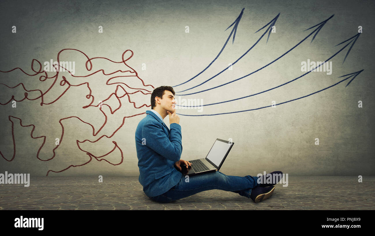 Imprenditore pensieroso seduto sul pavimento con il laptop, pensando a nuovi progetti. Concetto di elaborazione delle informazioni come linee mesh arrivano attraverso la testa Immagini Stock