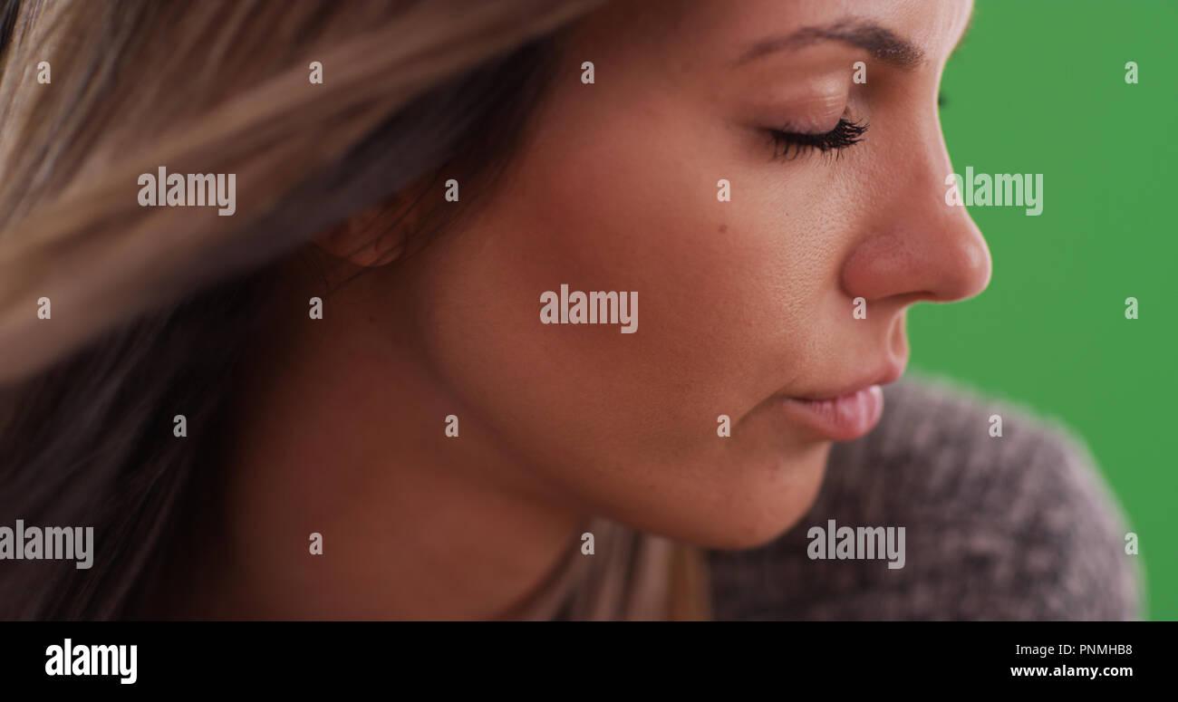 Stretto colpo di attraente giovane donna con gli occhi chiusi pensando a schermo verde Immagini Stock