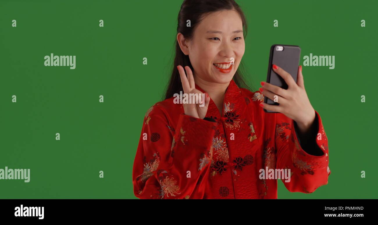 75c2d69fff4d Incantevole donna cinese in abito tradizionale prendendo selfie telefono su  schermo verde Immagini Stock
