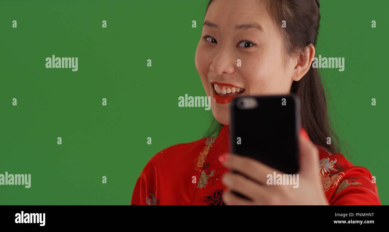9dc8b142ce29 Bella donna cinese in abito tradizionale tenendo selfie su schermo verde  Immagini Stock