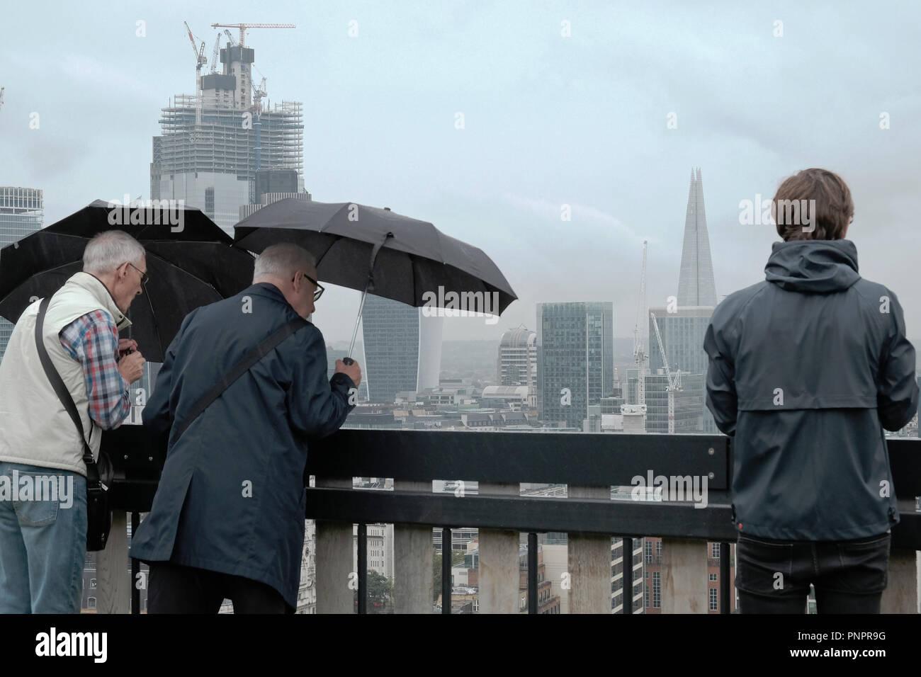 Regno Unito Meteo.1 Old Street cantiere, Old Street, Londra, Inghilterra. 22 Sett. 2018 Due uomini tenere gli ombrelli sotto la pioggia come guardano in vista di Londra dalla terrazza sul tetto al collare bianco fabbrica durante la Open House di Londra. Credito: Judi Saunders/Alamy Live News Immagini Stock