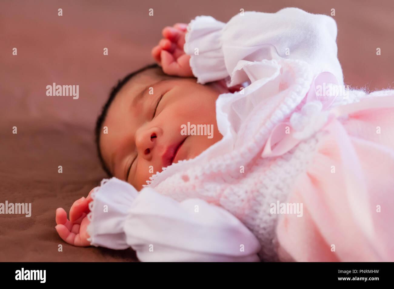 Carino a due settimane bambino neonato bambina indossa morbida maglia rosa vestiti, dormire serenamente nel letto Immagini Stock