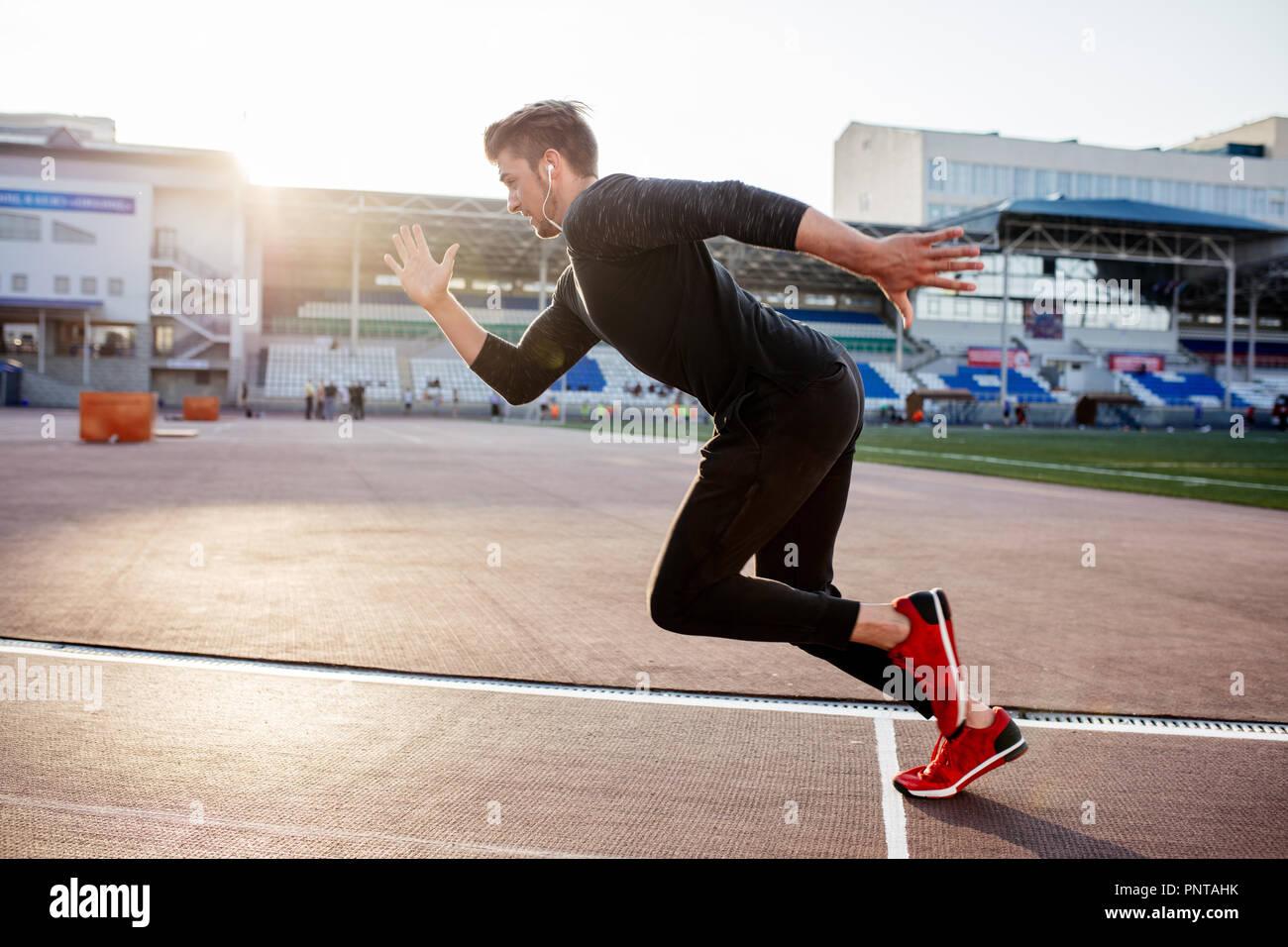 Atleta vestiti di nero a partire sprint su pista per la corsa Immagini Stock