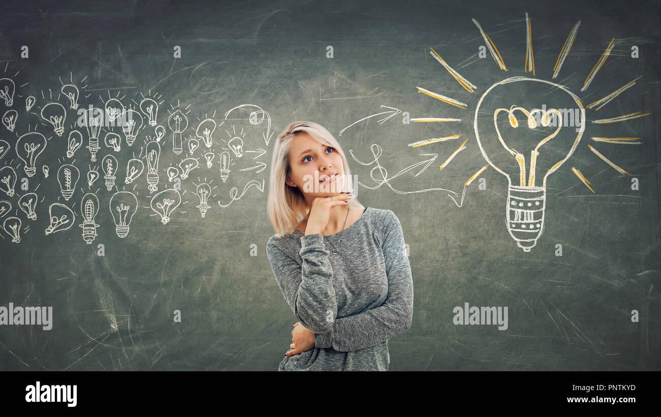 Il concetto di business come una ragazza pensieroso con la mano sotto il mento, pensando di raccogliere le idee in un grosso bulbo di luce. Immagini Stock