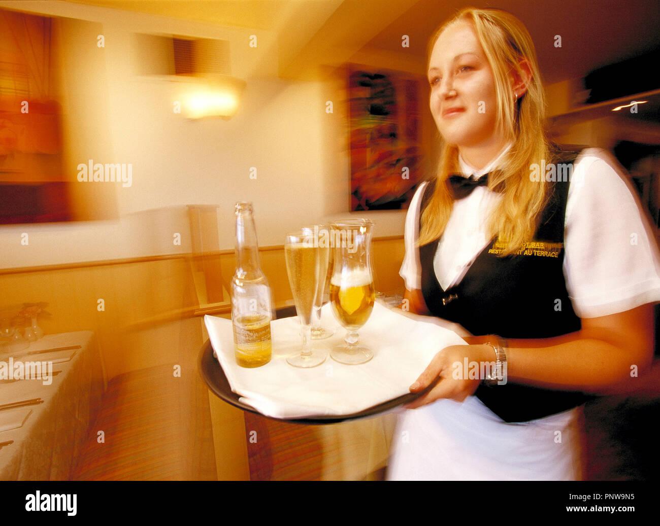 Giovane donna bionda cameriera con vassoio bevande nel ristorante café bar. Immagini Stock