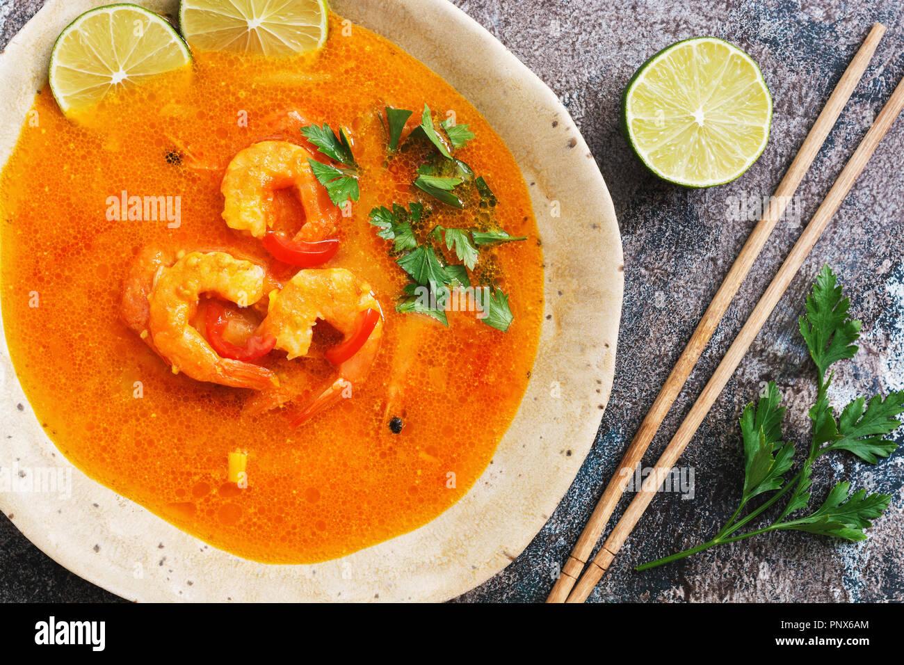 Piccante minestra acida con gamberi (Tom Yum Goong) su un sfondo rustico. Cibo tailandese. Vista da sopra, laici piatta Immagini Stock
