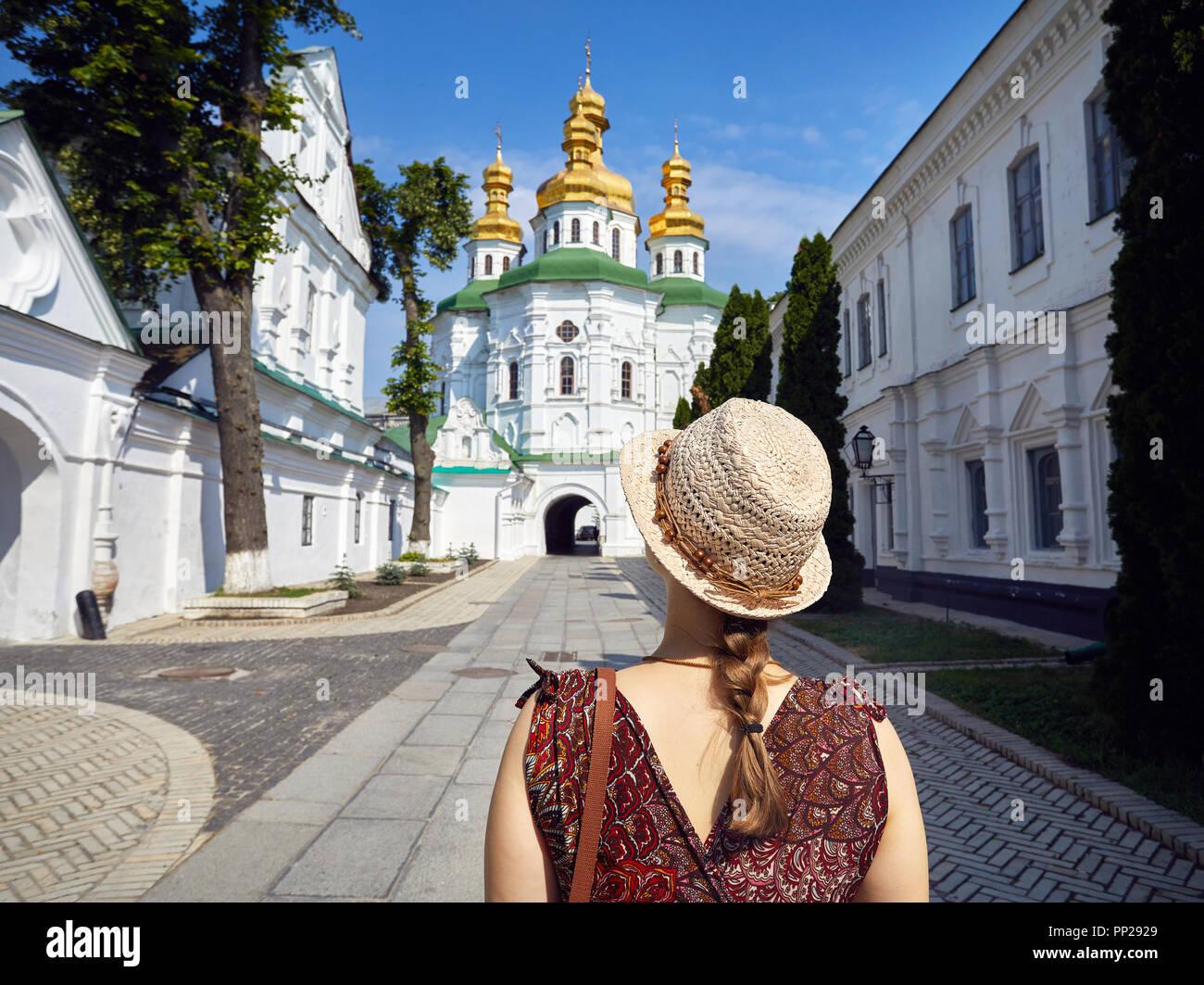 Donna in hat guardando alla Chiesa con cupole dorate a Kiev Pechersk Lavra complesso cristiano. Vecchia architettura storica a Kiev, Ucraina Immagini Stock